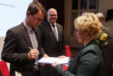 Matthias Schwarz unterschreibt für das FKH die Charta. Rechts Franziska Kopitzsch, Leiterin der Koordinierungsstelle.